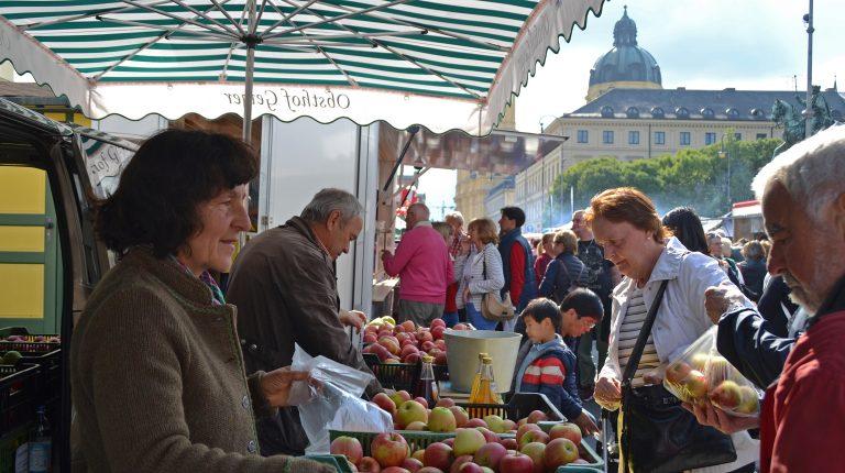 Eine Marktfrau verkauft Äpfel mit Theatinerkirche im Hintergrund